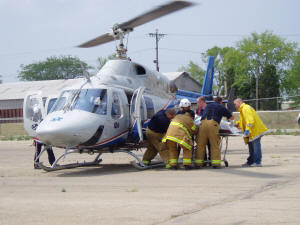 Firefighters load injured individual into helicopter